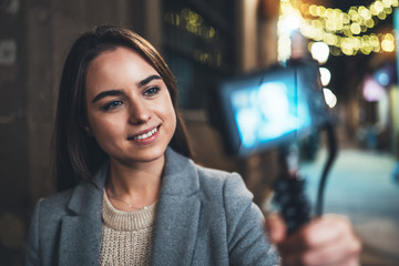 Fotomurales - Traveler female blogger shooting video for social media with digital camera. Smiling young woman vlogger taking  photo selfie on light night city