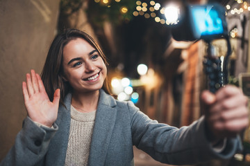 Fotomurales - Traveler female blogger shooting video for social media with digital camera showing hi. Smiling woman vlogger taking photo selfie on background light night city illuminations