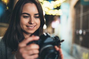 Fotomurales - Photographer girl take photo on background bokeh light in night city, Blogger photoshoot concept. Tourist  travels in Barcelona, photo hobby. Outdoor portrait of young smile woman with retro camera.