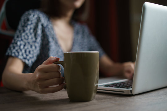 Woman working from home using computer and drinking cup of tea, closeup portrait indoor.