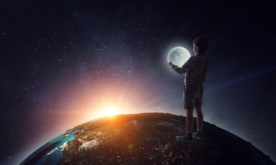 Boy holding moon at night
