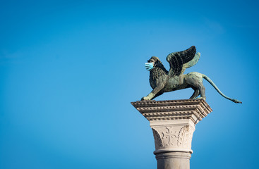 The Winged Lion of Venice wearing a face mask as a symbol of the Venice and Italy lockdown caused by coronavirus outbreak..