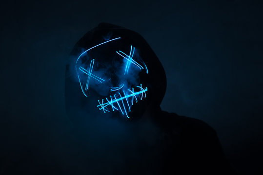 A man in a scary neon glowing mask and a hood on a dark background with smoke. Horror and Halloween concept