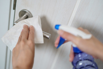 Woman hand using napkin and detergent spray cleaning doorknob for corona virus or Covid-19 protection.