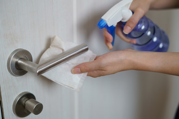 Woman hand using napkin and detergent spray cleaning doorknob for corona virus or Covid-19...