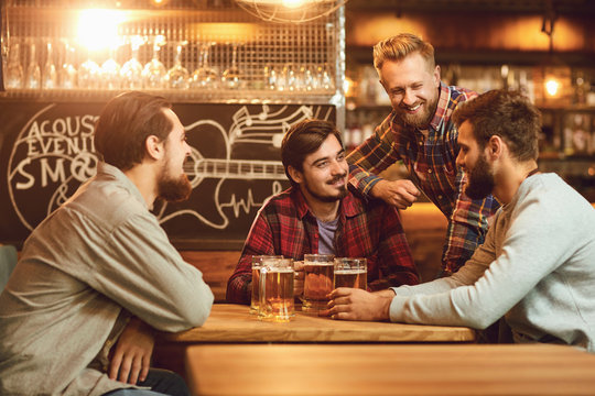 A group of friends is sitting in a bar with glasses of beer.