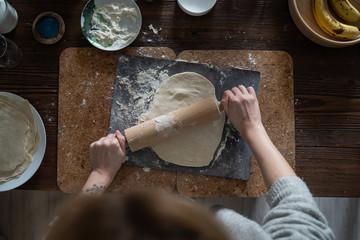 Fototapeta Kobieta robi ciasto. Wałkuje ciasto z mąką na drewnianym stole. obraz