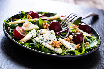 Fresh salad - blue cheese, grapes, spinach, walnuts on black stone board