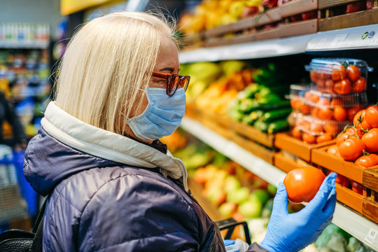 Old woman in medical masks is shopping in the supermarket looking for the food