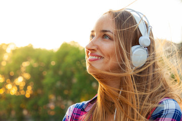 Beautiful young blonde woman with long hair and blue eyes listening to music with white headpones outside. Hands on headphones. Rome, Italy, Sunset.
