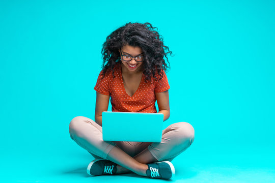 Beautiful young smiling woman in casual outfit and trendy eyeglasses sitting isolated on bright colored blue background and working on her laptop
