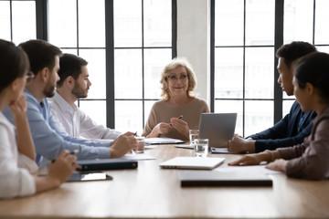 Confident middle-aged businesswoman lead office meeting with multiracial colleagues, happy senior...