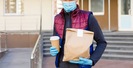 delivery man delivers orders. Delivery service under quarantine, disease outbreak, coronavirus covid-19 pandemic conditions.