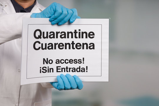 Doctor's hand in medical gloves showing English and Spanish quarantine sign in front of a restricted area