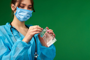 Close up of doctor holding swab with sample. Putting swab into transparent package. Isolated on green background. Fotobehang