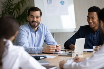 Smiling multiracial businesspeople sit at desk discuss cooperation with business partners clients,...