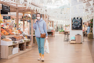 Woman in medical face mask walking in modern grocery market, shop. Corona virus protection,...