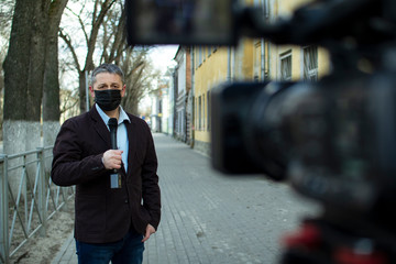 A middle- aged European journalist in a protective medical mask is reporting in a deserted city.