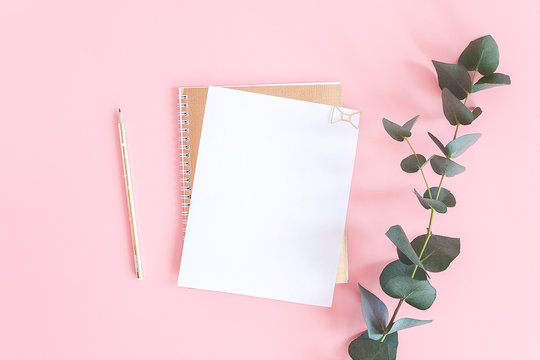 Blank white sheet on spiral golden notepad with paper clip heart, pencil and green branch of eucalyptus on pink pastel background. Mock up for your text and design. Top view Flat lay