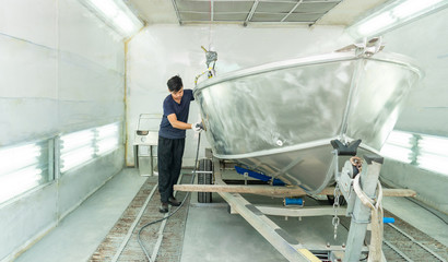 Aluminum boat painting procedure at service center ,The mechanic is using a metal grinder. , Surface preparation, boat body, for spray painting ship