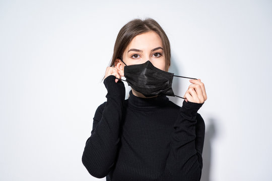 a girl in black clothes putting a black medicinal mask