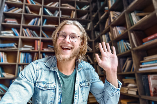 Cheerful male blogger influencer waving hand looking at camera recording video blog concept in library, happy young man laughing face shooting vlog for social media channel making video call concept.