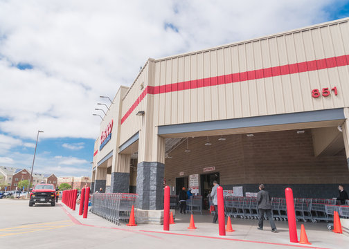 Side entrance of Costco Wholesale store in Lewisville, Texas with customer walking row of shopping carts