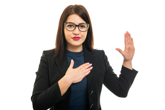 Portrait of young business girl wearing glasses making oath gesture