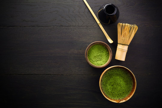 Matcha powder. Organic green matcha tea ceremony. Healthy drink. Traditional japanese drink on black wooden background
