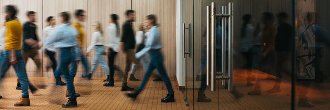 Group of business people walking at office openspace. Team of business employees at coworking center. People at motion blur. Concept working at action. Wide image