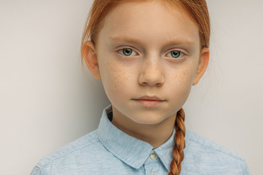 close-up portrait of serious caucasian red haired girl isolated over white background. people diversity, natural beauty concept