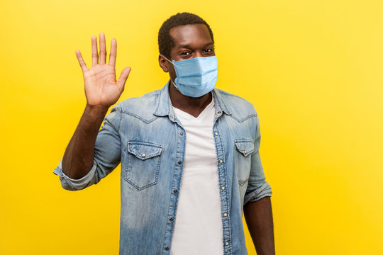 Hello! Portrait of positive handsome man with medical mask with rolled up sleeves smiling friendly and waving hand saying hi, welcoming gesture. indoor studio shot isolated on yellow background