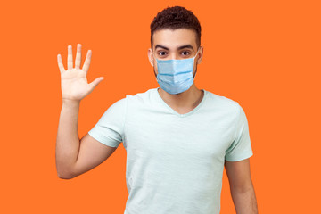 Hello! Portrait of friendly glad handsome man with medical mask in casual white t-shirt showing hi gesture with waving hand and smiling sincerely. indoor studio shot isolated on orange background Wall mural