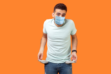 Portrait of frustrated worried man with medical mask in casual white t-shirt turning out empty...