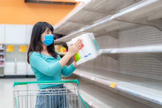 Asian woman looking at Supermarket empty toilet paper shelves amid COVID-19 coronavirus fears, shoppers panic buying and stockpiling toilet paper preparing for a pandemic.