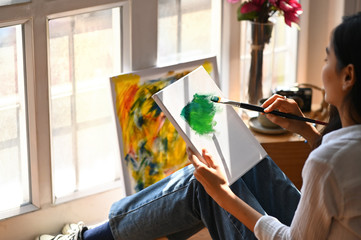 Photo of beautiful woman working as artist sitting on the floor while drawing/painting on drawing canvas over vintage art studio as background.