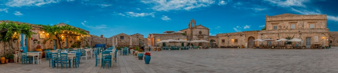 Panoramic view of the picturesque sicilian village Marzamemi, view of the traditional outdoor cafe and the church and the central square, province of Syracuse, Sicily, southern Italy Fototapete