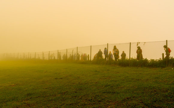 Trabzon / Turkey - August 07 2019: Silhouette of people walk behind the wire in a cold day under fog