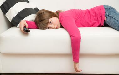 bored little girl lying on the sofa watches TV during the Coronavirus quarantine