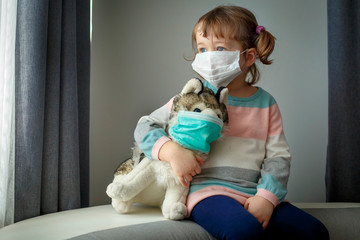 Quarantine at kindergarten. Toddler girl and her dog toy with protection masks. Coronavirus epidemic. Face mask for protection coronavirus outbreak. Medicine healthcare mask