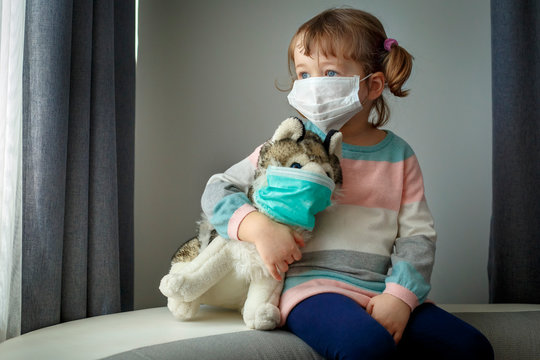 Quarantine at kindergarten. Toddler girl and her dog toy with protection masks. Coronavirus epidemic. Face mask for protection coronavirus outbreak. Medicine healthcare mask