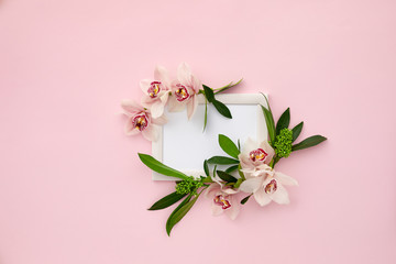Tuinposter Orchidee photo frame decorated with green leaves and orchid flowers on pink pastel background. empty space for text. mock up with copy space. Flat lay
