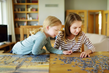 Cute young girls playing puzzles at home. Children connecting jigsaw puzzle pieces in a living room table. Kids assembling a jigsaw puzzle. Fun family leisure.
