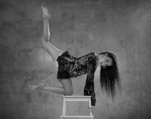Beautiful acrobatic in white lace lingerie posing on the wooden chair stepladder in the studio over concrete wall background - black and white photography