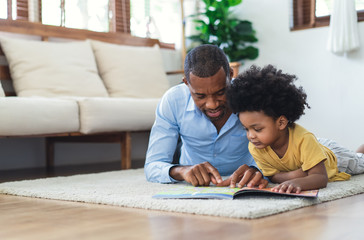 Happy African American father and son are reading a book and smiling while lying on floor spending...