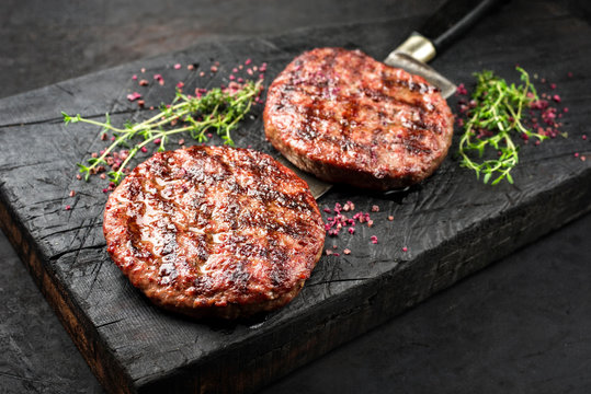 Barbecue Wagyu Hamburger with red wine salt and herbs as closeup on a charred wooden board