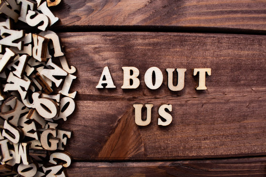 """The word """"About us"""" spelt out with wooden letters on the wooden background. Business, communication concept."""