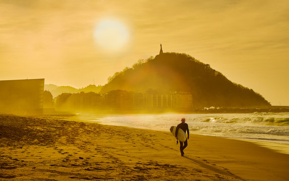 A surfer walking on the Zurriola Beach at sunset with the Monte Urgull in the background. San Sebastian, Basque Country, Guipuzcoa. Spain.