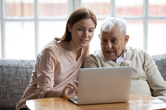 Grown-up daughter and old 80s father choose goods or services via internet or web surfing together at home. Younger generation caring about older relatives teaching using computer useful apps concept