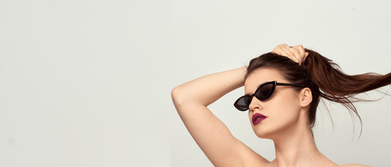beautiful young girl with brown hair in fashionable glasses posing on a white background with bare shoulders, empty space for text Wall mural